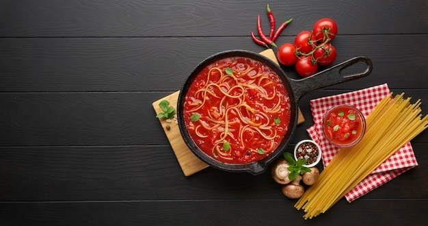 Homemade boiling italian pasta with tomato sauce in cast iron pan served with red chili pepper, fresh basil, cherry-tomatoes and spices over black rustic wooden table, cooking food concept