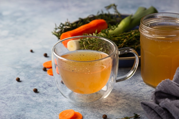 Homemade bone broth in glass mug and vegetables. collagen source for the body.
