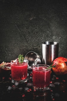 Homemade boozy alcoholic pomegranate cocktail with rosemary and vodka, dark rusty metal ,
