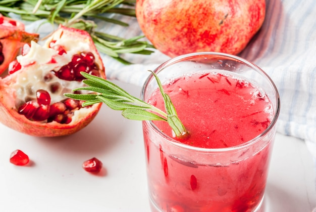 Homemade boozy alcoholic pomegranate cocktail with rosemary and vodka, white marble ,