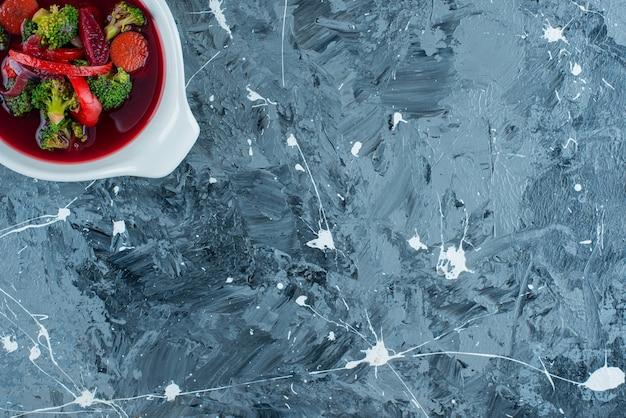 파란색 배경에 그릇에 만든 돼지 고기 수프.