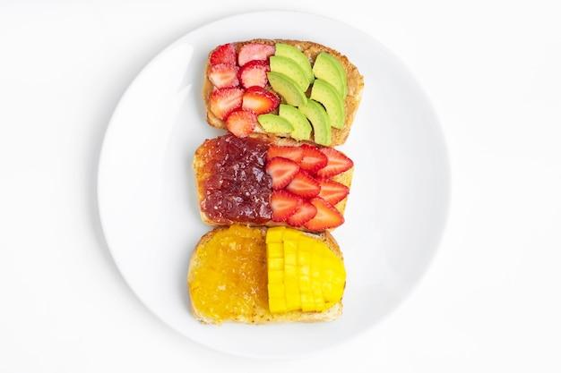Домашний хлеб, покрытый арахисовым маслом, апельсиновым джемом и клубничным вареньем с клубникой, манго и авокадо на белой тарелке. здоровое питание для похудения. концепция здорового завтрака.
