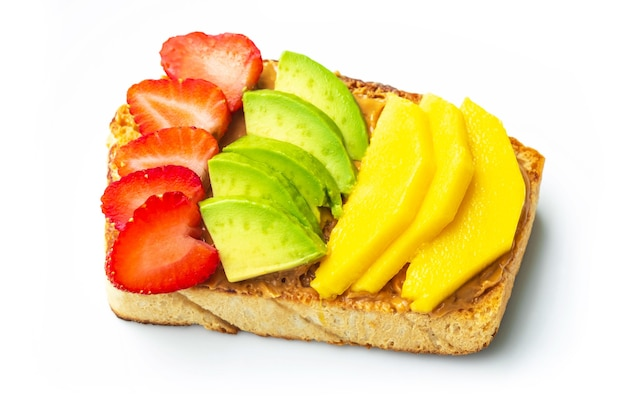 Homemade bread covered with peanut butter, top with strawberries, mango and avocado on white plate. healthy food for weight loss. healthy breakfast concept.
