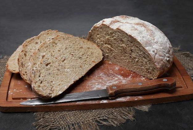 Домашний хлеб из муки грубого помола со специями, нарезанный на деревянной доске с семечками льна и подсолнечника. выпечка дрожжевого хлеба на закваске, безглютеновый диабетический хлеб.