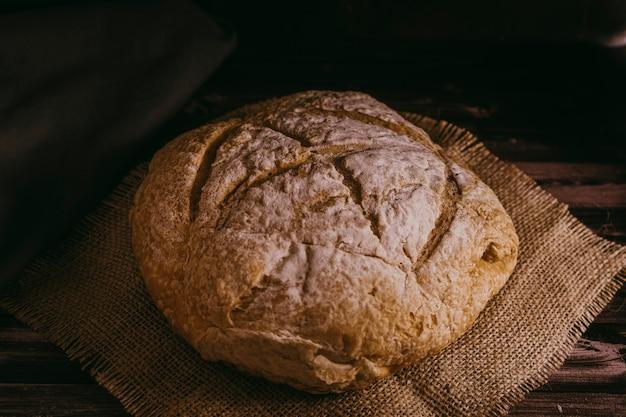 수제 빵은 소박한 표면에서 지속됩니다. 어두운 배경입니다. 풍경 보기입니다.