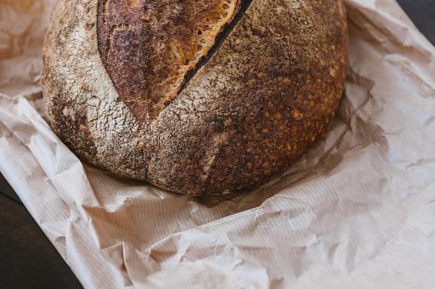 キッチンテーブルのクラフト紙に自家製パンクリスピー焼き小麦パン表面テクスチャ選択フォーカス