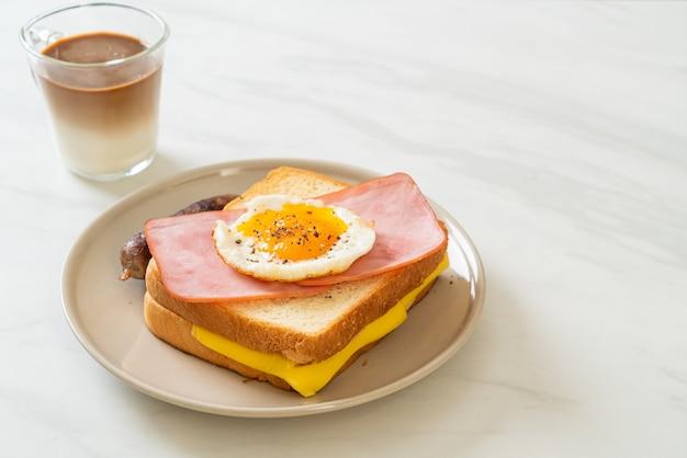 Домашний хлеб, обжаренный с сыром, ветчиной и жареным яйцом со свиной колбасой и кофе на завтрак