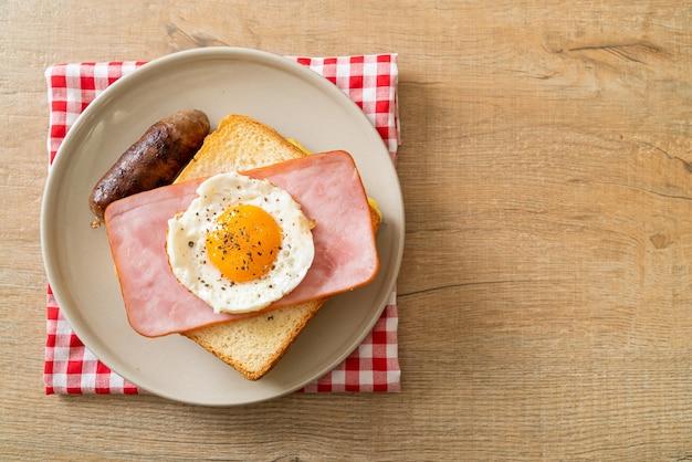 朝食に自家製パントーストチーズトッピングハムと目玉焼きとポークソーセージ