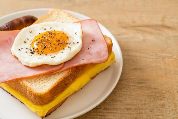 Домашний хлеб, обжаренный с сыром, ветчиной и жареным яйцом со свиной колбасой на завтрак