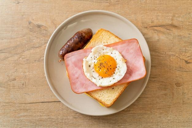 Домашний хлеб, обжаренный с сыром, ветчиной и жареным яйцом со свиной колбасой на завтрак Premium Фотографии