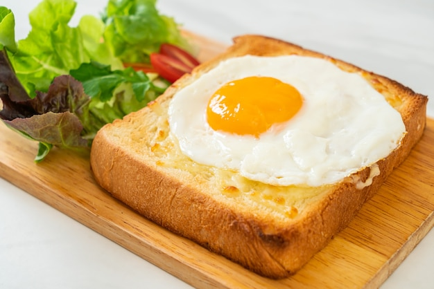 Домашний хлеб, обжаренный с сыром и жареным яйцом сверху, с овощным салатом на завтрак