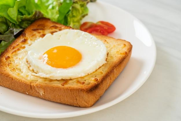 朝食にチーズと目玉焼きをのせてトーストした自家製パンに野菜サラダを添えて