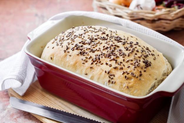 Домашний хлеб с семенами льна в красной керамической форме для выпечки
