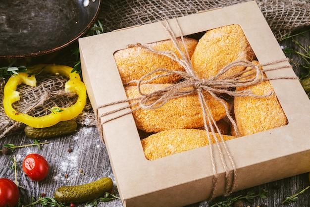 Домашние сырые котлеты в панировке в коробке на деревянном столе в деревенском стиле. здоровая пища.