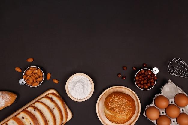 Homemade breads ingredients, flour, almond nuts, hazelnuts, eggs on dark background.
