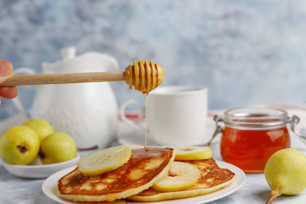 Homemade breakfast: american style pancakes served with pears and honey with a cup of tea on concrete . top view and copy
