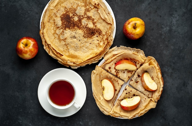 テキストのコピースペースと石の背景にリンゴとお茶と薄いパンケーキの自家製朝食