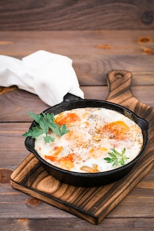 Homemade breakfast of shakshuka fried eggs with tomatoes and herbs in a pan on a wooden table