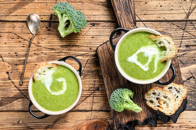 Homemade broccoli and spinach cream soup in bowl. wooden background. top view.