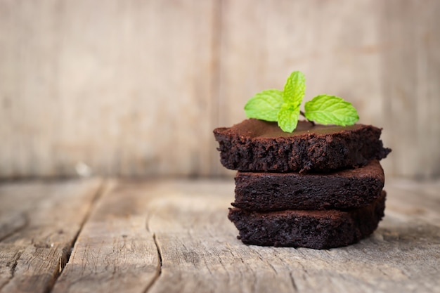 Homemade brownie served with chocolate fudge. sweet dessert on wooden background.