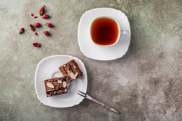 木製のテーブルにフォークが付いた受け皿にアーモンドを添えた自家製ブラウニー。