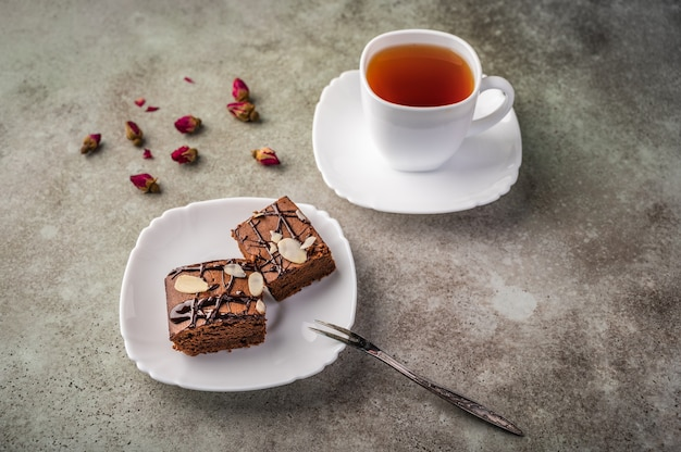 Homemade brownie with almonds on a saucer with a fork on wooden table.