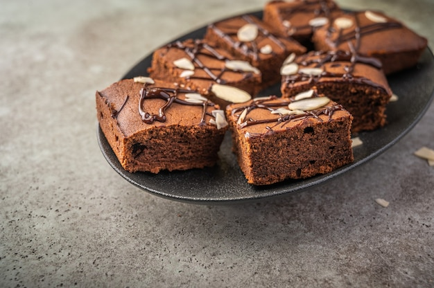 Homemade brownies with almond petals on a dark plate on a wooden background.