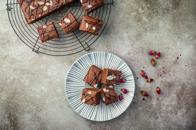 Homemade brownies with almond petals and rosebuds on a textured plate on a wooden background.
