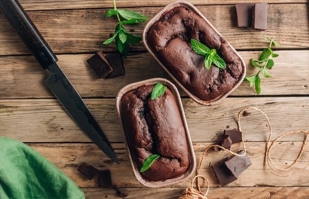 ダークチョコレートと素朴な木製の背景にミントの自家製ブラウニー。小分けのグラタン皿。上面図