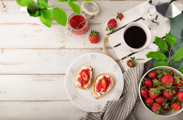 흰색 나무 배경에 코티지 치즈와 딸기를 곁들인 홈메이드 브루스케타
