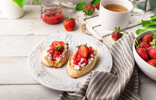Homemade bruschetta with cottage cheese and strawberries at white wooden background