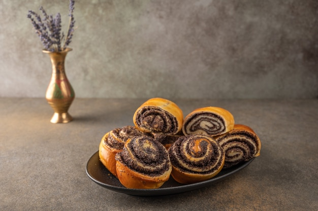 Homemade buns with poppy seeds on a black plate and a bowl of lavender on a dark background close-up.