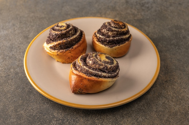 Homemade buns with poppy seeds on a light plate on a dark background close-up.