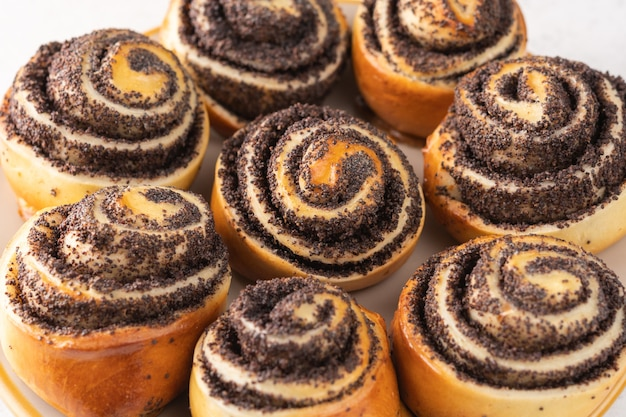 Homemade buns with poppy seeds on a light surface close-up