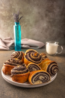 Homemade buns with poppy seeds on a white plate bowl of lavender and cap with milk on a dark background closeup selective focus
