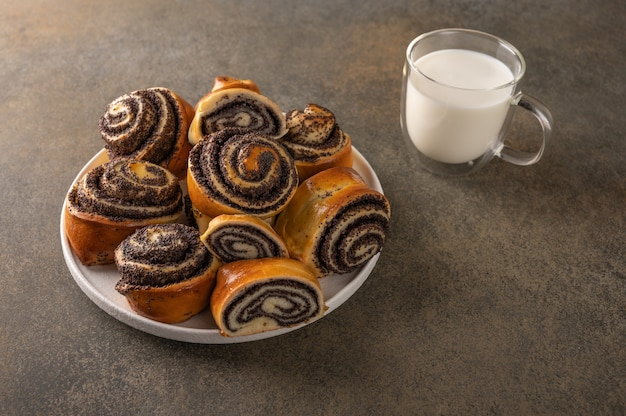 Homemade buns with poppy seeds on a white plate and cap with milk on a dark background.