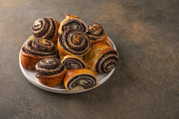 Homemade buns with poppy seeds on a white plate on a dark background close-up.