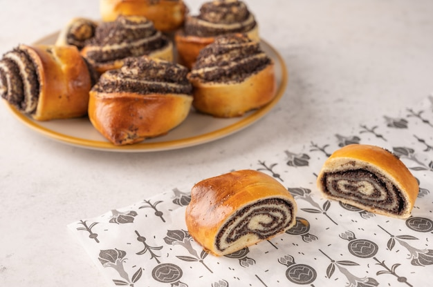 Homemade buns with poppy seeds on a white plate on a light background close-up.