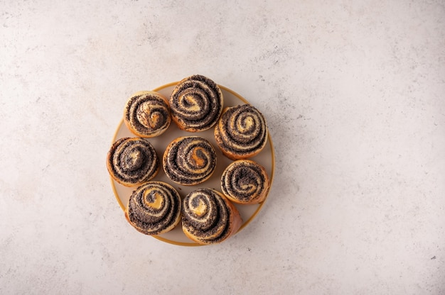 Homemade buns with poppy seeds on a white plate on a light background top view.