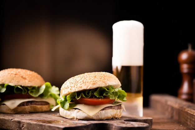 Домашний бургер и стакан пива на деревянном фоне