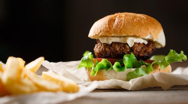 Домашний гамбургер и картофель на деревянной тарелке