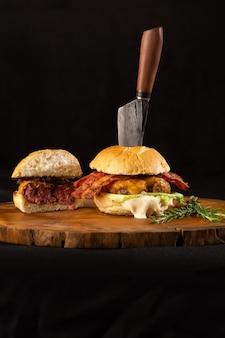Домашний бургер, гамбургер с плавленым сыром, салат, бекон, трава розмарина на деревенском столе и нож