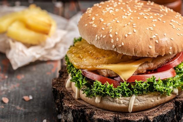 素朴な木製の背景に牛肉のグリル、野菜、ソースを添えた自家製ハンバーガー。ファーストフードとジャンクフードのコンセプト