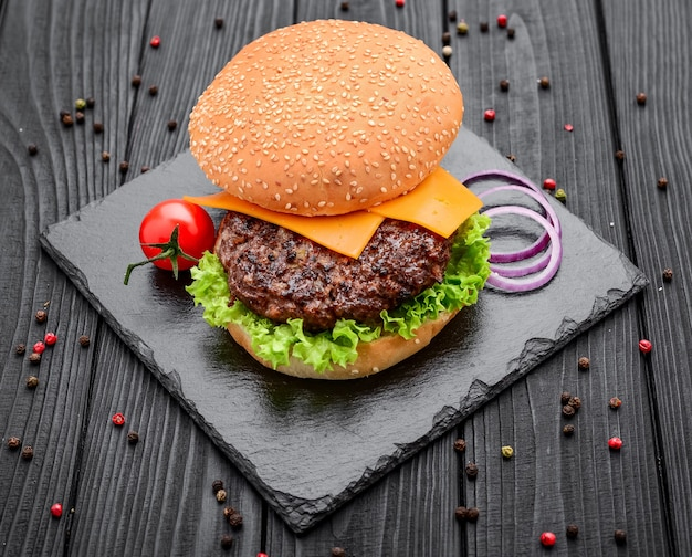 Homemade burger with salad and cheese on black slate