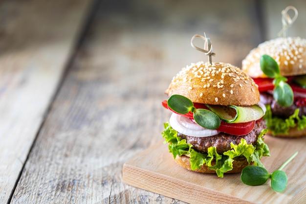 Домашние гамбургеры с котлетой, свежим салатом, помидорами, луком на деревянном столе. копировать пространство