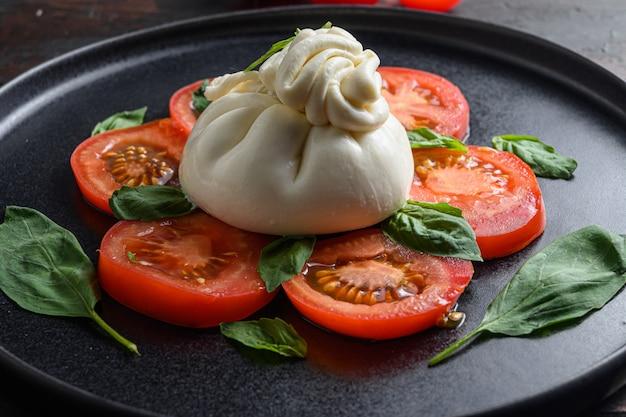 신선한 토마토와 바질 잎을 곁들인 수제 부라 타 치즈
