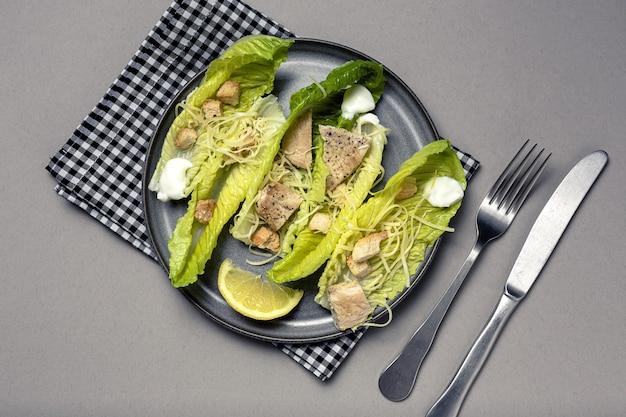 Домашний салат «цезарь» с романином, сыром, гренками, курицей, лимоном и соусом.