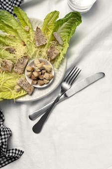 Homemade caesar salad with romanine, cheese, croutons, chicken, lemon and sauce. on white linen tablecloth