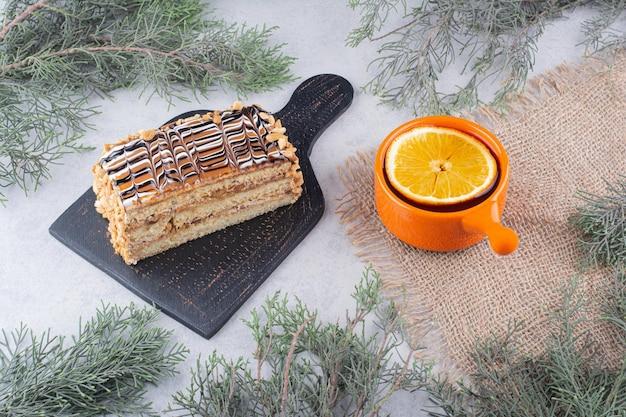 Домашний торт и чашка чая на мраморной поверхности с сосновой веткой. фото высокого качества
