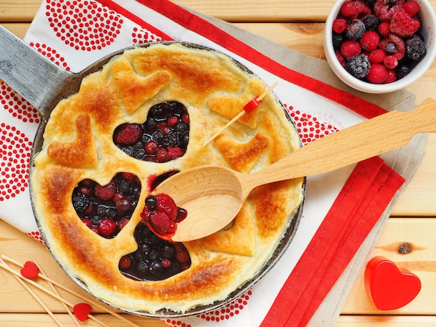 Homemade cake closeup with raspberries, red currants and blueberries in shape of heart on wooden surface